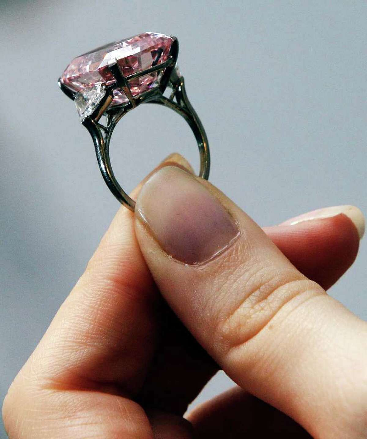 LONDON, ENGLAND - OCTOBER 25: A 24.78 Carat Fancy Intense Pink Diamond, estimated to be worth USD27-38 million is modelled by Sotheby's Jewellery employee Jessica Wyndham at Sotheby's auction house on October 25, 2010 in London, England. The diamond is currenty part of a display but will be auctioned on November 16th at Sotheby's in Geneva. (Photo by Matthew Lloyd/Getty Images)