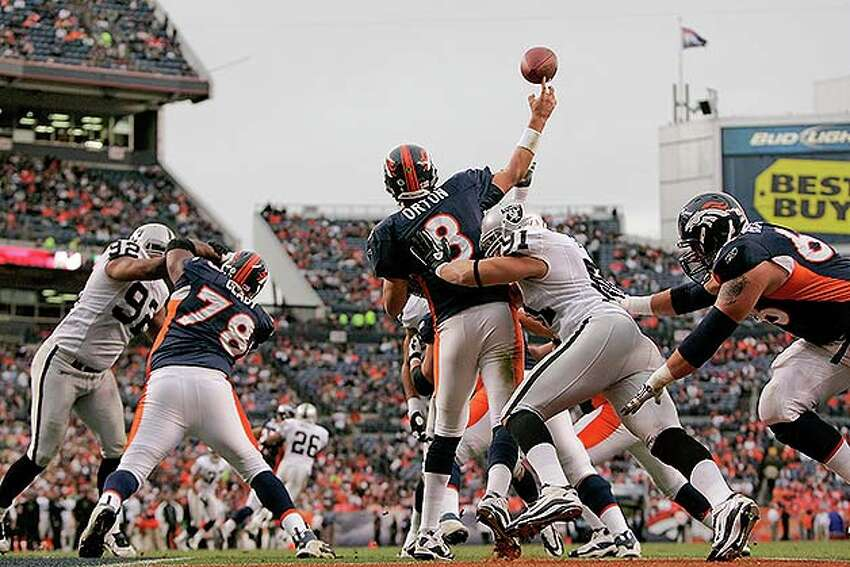 DENVER - OCTOBER 24: Quarterback Kyle Orton #8 of the Denver Broncos is hit as he makes a pass from his own end zone by defensive end Trevor Scott #91 of the Oakland Raiders at INVESCO Field at Mile High on October 24, 2010 in Denver, Colorado. The Raiders defeated the Broncos 59-14. (Photo by Justin Edmonds/Getty Images) *** Local Caption *** Kyle Orton;Trevor Scott