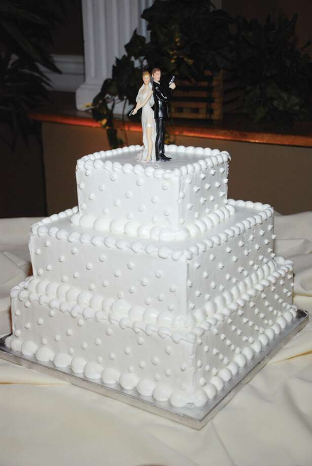 (Sharon Mahar/VOW) The bride and groom?s cake topper was inspired by the movie Mr. and Mrs. Smith.