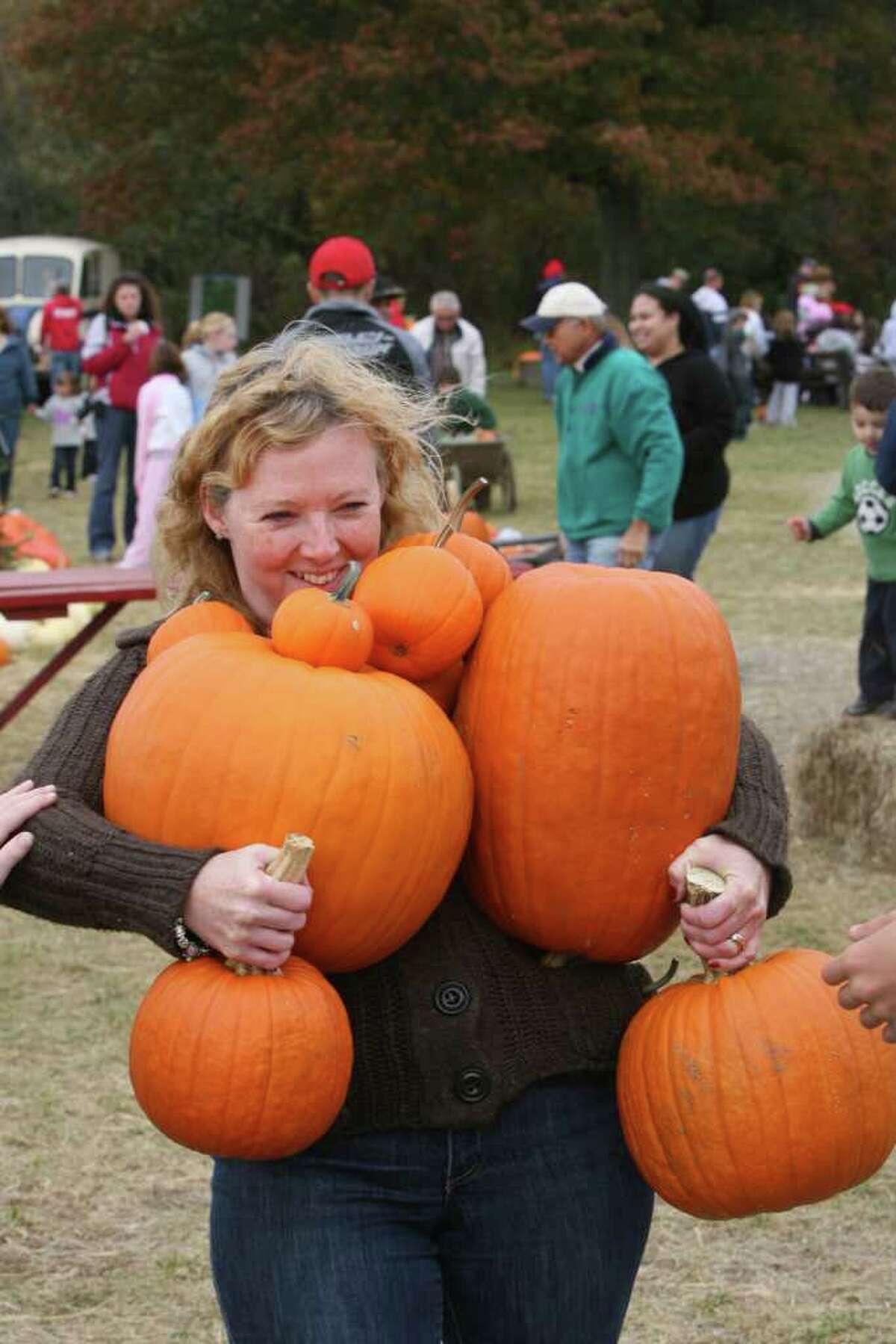 Nora Dorso, of Lindenhurst, NY, carries as many pumpkins as she can at the Jones Tree Farm UNICEF Family Festival on Sunday, October 24, 2010.