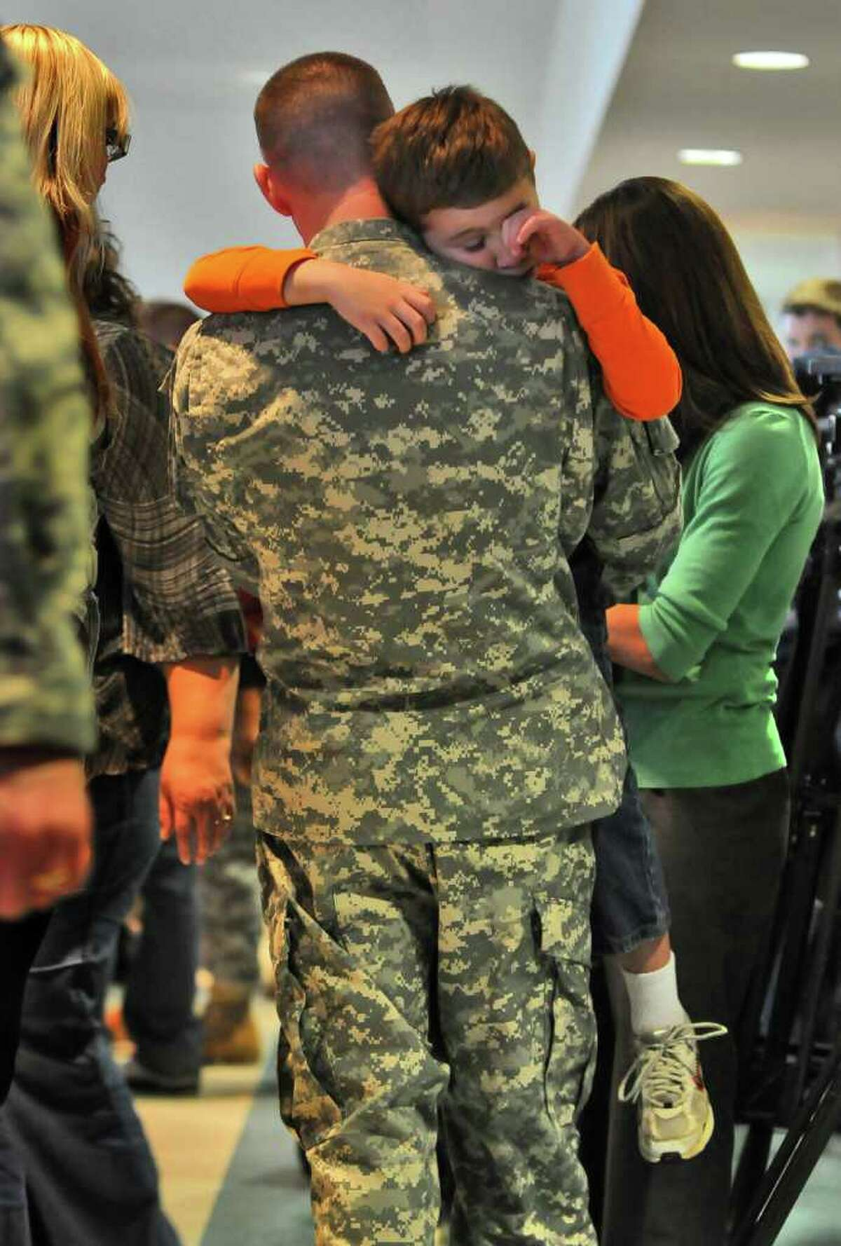 Staff Sgt. Shawn Nethaway of Latham tries to comfort his son Logan, 7, following a mobilization farewell ceremony for the Headquarters, 501st Ordnance Battalion at the Stratton Air National Guard Base in Glenville on Monday, October 25, 2010. The unit is heading to Iraq after training. This is Staff Sgt. Nethaway's second deployment.( Philip Kamrass / Times Union )