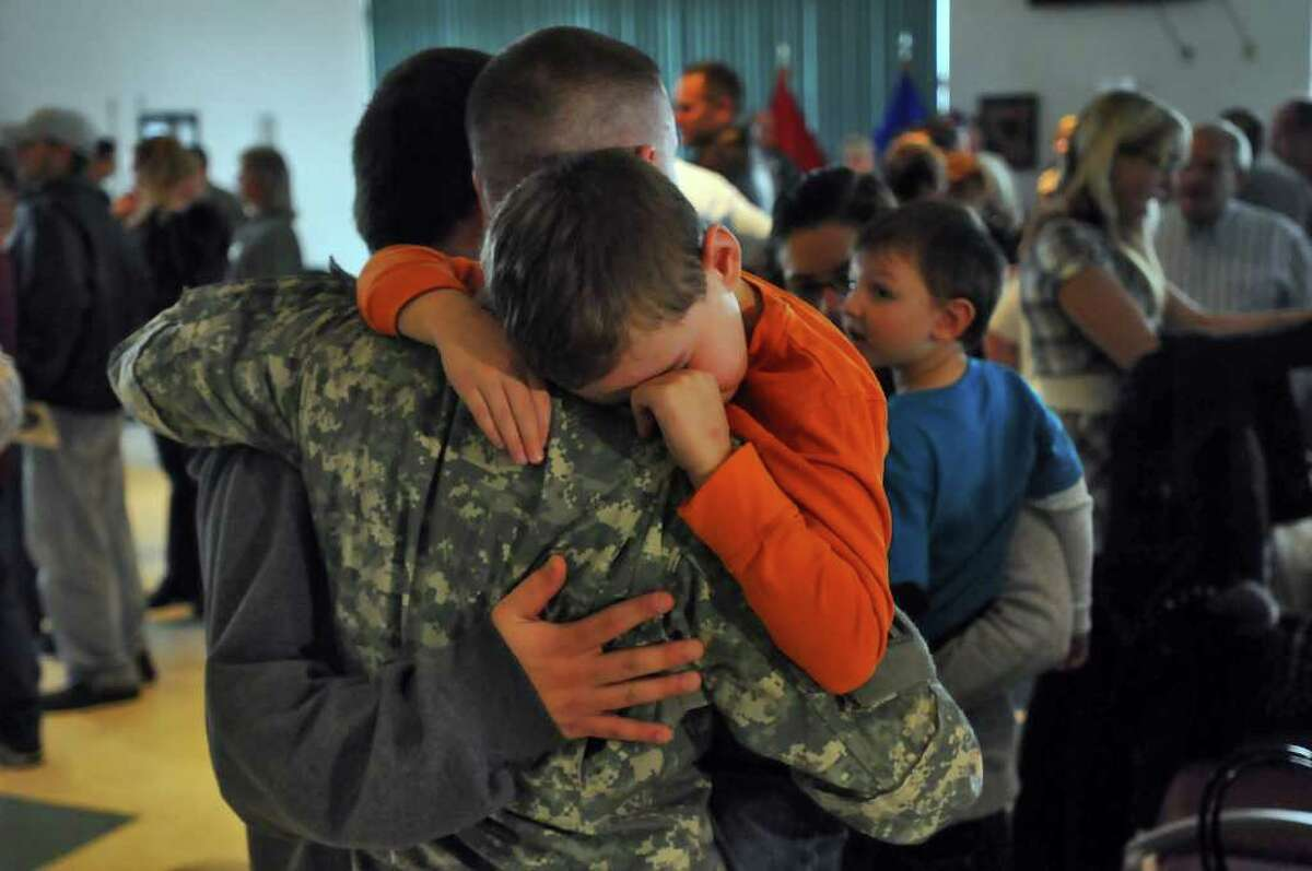 Staff Sgt. Shawn Nethaway of Latham tries to comfort his son Logan, 7, following a mobilization farewell ceremony for the Headquarters, 501st Ordnance Battalion at the Stratton Air National Guard Base in Glenville on Monday, October 25, 2010. The unit is heading to Iraq after training. This is Staff Sgt. Nethaway's second deployment. ( Philip Kamrass / Times Union )