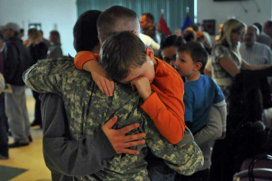 Staff Sgt. Shawn Nethaway of Latham tries to comfort his son Logan, 7, following a mobilization farewell ceremony for the Headquarters, 501st Ordnance Battalion at the Stratton Air National Guard Base in Glenville on Monday, October 25, 2010. The unit is heading to Iraq after training. This is Staff Sgt. Nethaway's second deployment. ( Philip Kamrass / Times Union ) Photo: Philip Kamrass