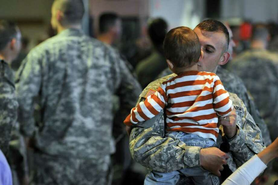 Sgt. 1st class Kevin Williams of Delmar kisses his son Weston, 1, before a mobilization farewell ceremony for the Headquarters, 501st Ordnance Battalion at the Stratton Air National Guard Base in Glenville, NY on Monday October 25, 2010. The unit is heading to Iraq after training. ( Philip Kamrass / Times Union ) Photo: Philip Kamrass
