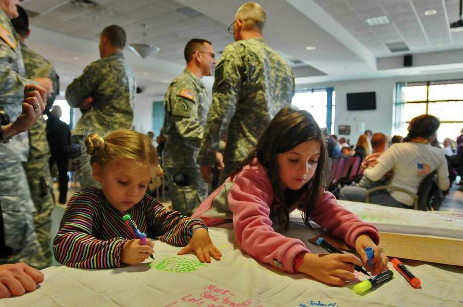 Sophia Chiancone, 4, left, and her sister Olivia, 8, right, both of North Carolina, sign a flag  before a mobilization farewell ceremony for the Headquarters, 501st Ordnance Battalion at the Stratton Air National Guard Base in Glenville, NY on Monday October 25, 2010. Their father, Capt. Tom Chiancone, is part of the unit. The unit is heading to Iraq after training, and the flag will be displayed there. ( Philip Kamrass / Times Union ) Photo: Philip Kamrass
