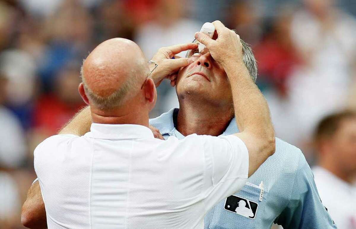 ATLANTA - JUNE 30: Trainer Jeff Porter (left) of the Atlanta Braves attends to the right eye of homeplate umpire John Hirschbeck #17 (right) during the game against the Washington Nationals at Turner Field on June 30, 2010 in Atlanta, Georgia. (Photo by Kevin C. Cox/Getty Images) *** Local Caption *** Jeff Porter;John Hirschbeck