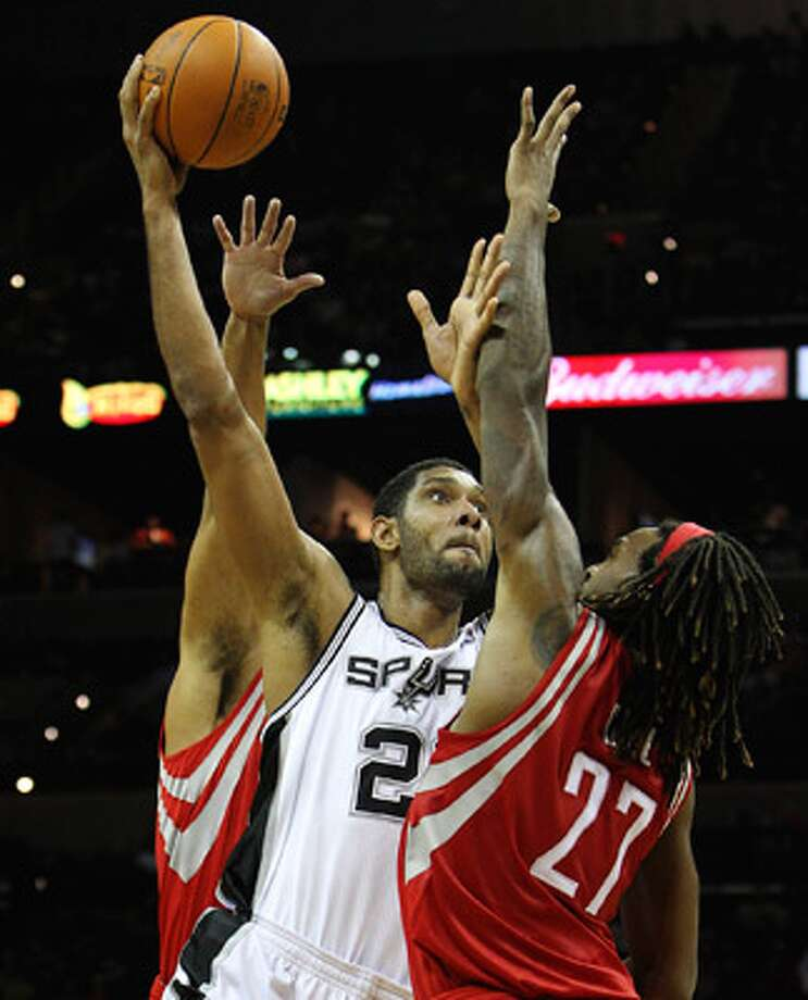 The Spurs' Tim Duncan (center) puts up a shot over the Rockets' Jordan Hill (27) in Thursday's preseason game.