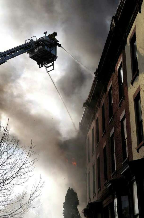 Firefighters fight a blaze at the three-story brownstone at 149 Second St. near the Washington Park neighborhood.  The  home is owned by Joyce and John Chupka. Joyce Chupka is president of the historical society and active in community affairs.  Albany and Watervliet firefighters are helping to battle the blaze.  (Paul Buckowski / Times Union) Photo: Paul Buckowski