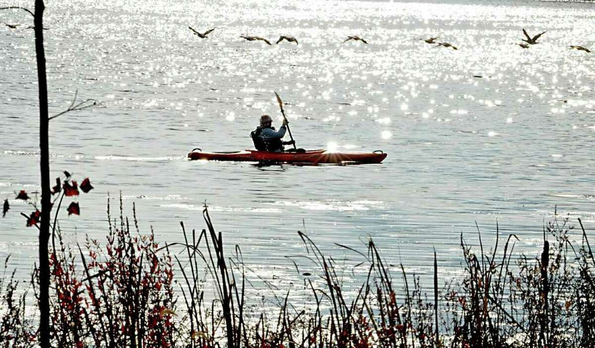A kayaker watches a flock of geese fly over him while out for a paddle on Cossayuna Lake in Cossayuna, NY on October 26, 2010. (Lori Van Buren / Times Union)
