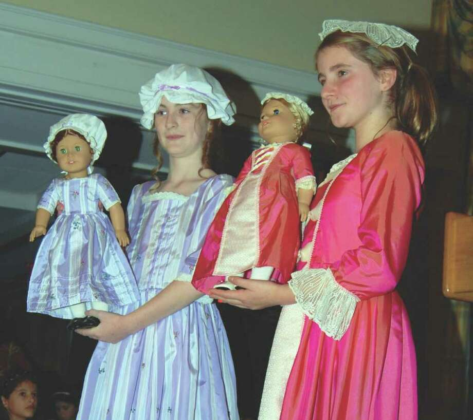 Two girls pose with their dolls during the fashion show. Photo: Jeanna Petersen Shepard / New Canaan News