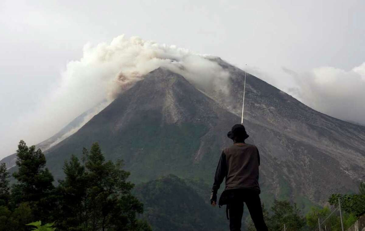 A volunteer watches as Mount Merapi spews volcanic smoke in the background in Kaliadem, Yogyakarta, Indonesia, Tuesday, Oct. 26, 2010. Indonesia's most volatile volcano started erupting Tuesday, after scientists warned that pressure building beneath its dome could trigger the most powerful eruption in years. (AP Photo/Gembong Nusantara)