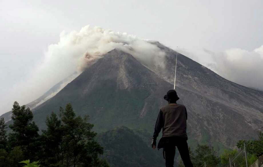 A volunteer watches as Mount Merapi spews volcanic smoke in the background in Kaliadem, Yogyakarta, Indonesia, Tuesday, Oct. 26, 2010. Indonesia's most volatile volcano started erupting Tuesday, after scientists warned that pressure building beneath its dome could trigger the most powerful eruption in years. (AP Photo/Gembong Nusantara) Photo: Gembong Nusantara