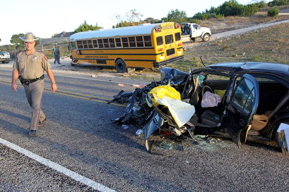 A Texas Department of Public Safety trooper crosses Texas 46 at the spot where a car collided with a Uvalde Consolidated Independent School District bus about 5 miles west of Boerne.