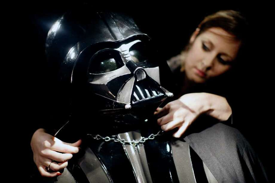 LONDON, ENGLAND - OCTOBER 27:   Christie's employee Caitlin Graham with an original Darth Vader costume from the Star Wars films on display in Christie's auction house on October 27, 2010 in London, England. The rare collectors piece is expected to realise between GBP160,000 and GBP230,000.  (Photo by Matthew Lloyd/Getty Images) Photo: Matthew Lloyd, Getty Images / 2010 Getty Images