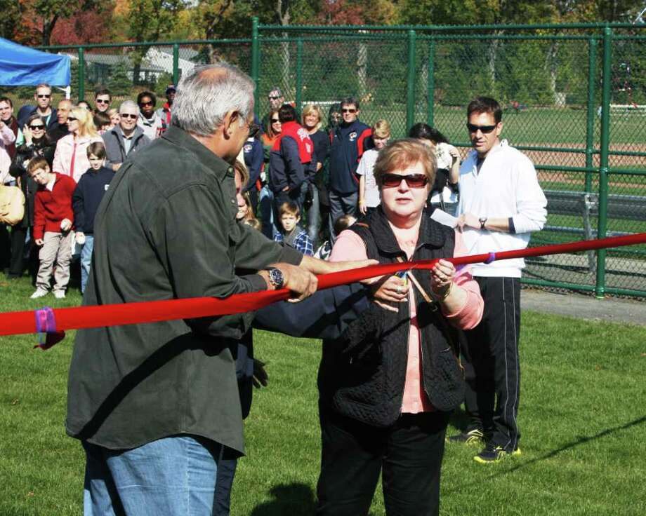 Fairfield resident  GFA Board memeber and chair of the Buildings and Grounds committee, Steve Lawrence, and Janet Hartwell, Head of School, cut the ribbon for the new baseball infield and tennis courts at GFA on Saturday as ESPN's Mike Greenberg looks on. Photo: Contributed Photo;Contributed Photo, Contributed Photo / Fairfield Citizen contributed