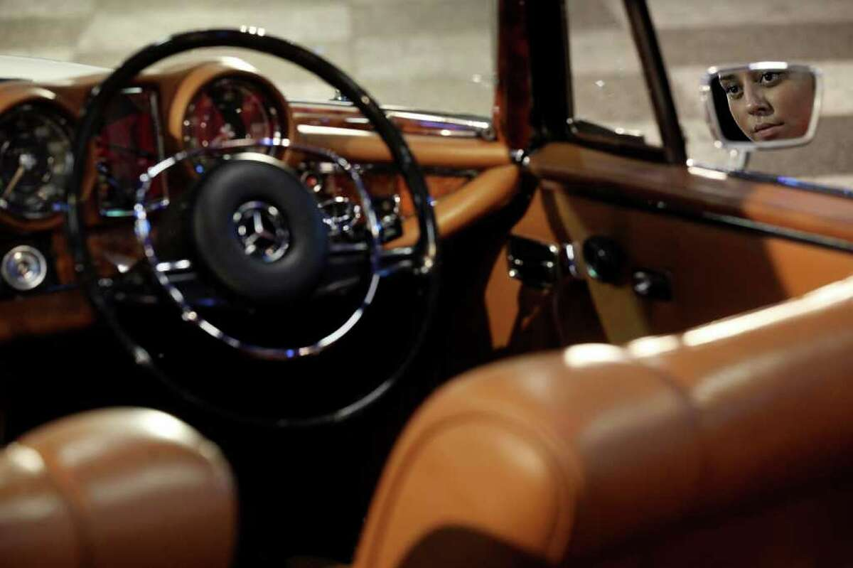 LONDON, ENGLAND - OCTOBER 27: A woman admires a 1971 Mercedes-Benz 280SE 3.5 Cabriolet, which is up for auction with an estimated sale price of 100,000 GBP, at the 'Automobiles of London' rare car auction in Battersea Park on Ocotber 27, 2010 in London, England. Over 100 motor cars are to be auctioned including the original Aston Martin DB5 driven by Sean Connery in Goldfinger and Thunderball James Bond films which is expected to fetch over 3.5 million GBP. (Photo by Oli Scarff/Getty Images)