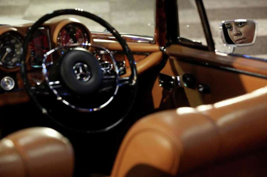 LONDON, ENGLAND - OCTOBER 27:  A woman admires a 1971 Mercedes-Benz 280SE 3.5 Cabriolet, which is up for auction with an estimated sale price of 100,000 GBP, at the 'Automobiles of London' rare car auction in Battersea Park on Ocotber 27, 2010 in London, England. Over 100 motor cars are to be auctioned including the original Aston Martin DB5 driven by Sean Connery in Goldfinger and Thunderball James Bond films which is expected to fetch over 3.5 million GBP.   (Photo by Oli Scarff/Getty Images) Photo: Oli Scarff, Getty Images / 2010 Getty Images