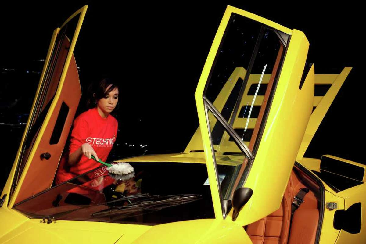 LONDON, ENGLAND - OCTOBER 27: A woman cleans a 1975 Lamborghini Countach LP400 'Periscopo', which is up for auction with an estimated sale price of 240,000 GBP, at the 'Automobiles of London' rare car auction in Battersea Park on Ocotber 27, 2010 in London, England. Over 100 motor cars are to be auctioned including the original Aston Martin DB5 driven by Sean Connery in Goldfinger and Thunderball James Bond films which is expected to fetch over 3.5 million GBP. (Photo by Oli Scarff/Getty Images)