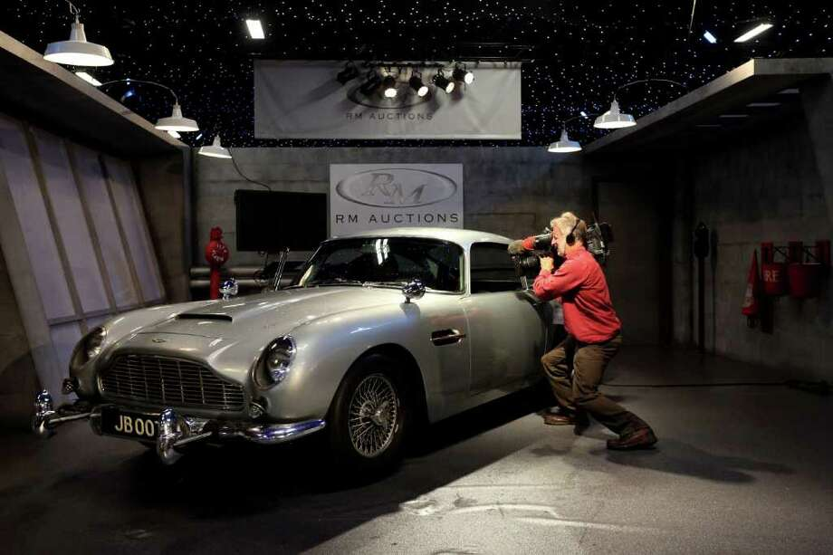 LONDON, ENGLAND - OCTOBER 27:  A cameraman films the 1964 Aston Martin DB5 used in the Goldfinger and Thunderball films, prior to featuring in the 'Automobiles of London' rare car auction in Battersea Park on Ocotber 27, 2010 in London, England. Over 100 motor cars are to be auctioned including the original Aston Martin DB5 driven by Sean Connery in Goldfinger and Thunderball James Bond films which is expected to fetch over 3.5 million GBP.  (Photo by Oli Scarff/Getty Images) Photo: Oli Scarff, Getty Images / 2010 Getty Images