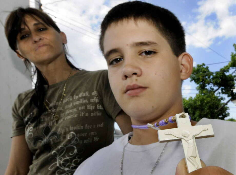 In this May photograph, Raymond Hosier with his mother, Chantell Hosier, shows the rosary he was wearing when Schenectady school officials sent him home from school. (Mike Farrell / Times Union)