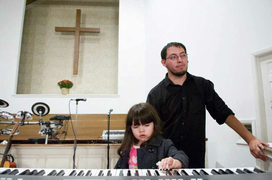 Amber Rojas, 2, practices her keyboarding skills with her father Andres as members of the Church of the Nazarene congregation gather at the Evangelical Community Church on Newfield Avenue Tuesday, October 24, 2010. Photo: Keelin Daly / Stamford Advocate