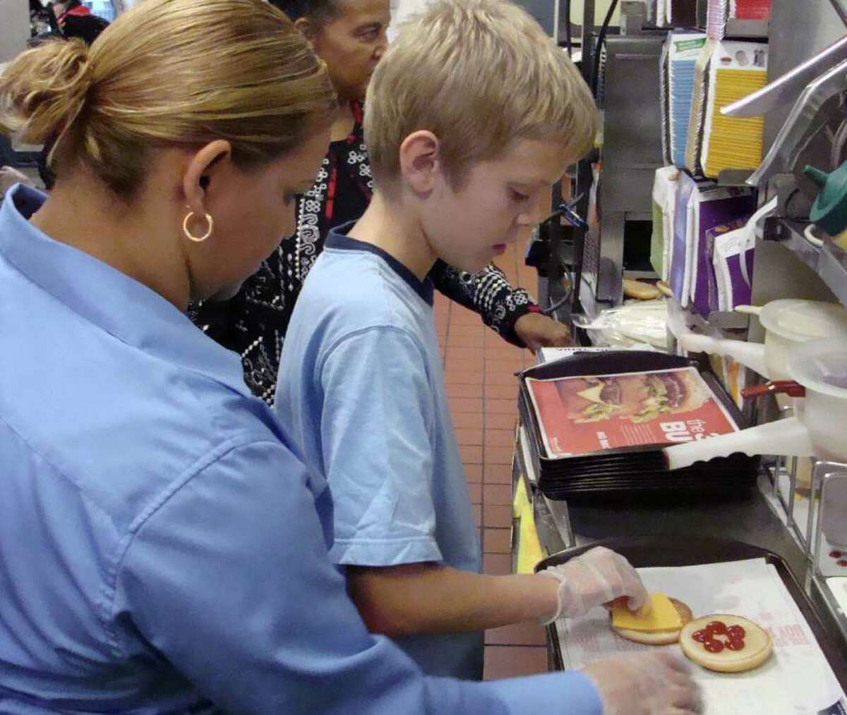 Jack Kyzer, 11, of Stratford, a 6th grade student at Eli Whitney School, gets help from Maria Pagan, store manager at McDonald's restaurant on 2439 Barnum Avenue, as he builds his own hamburger sandwich. In the background is Gail Grant, a local store marketer for McDonald's, who taught Jack and his classmates about making healthy meal choices and developing nutritionally sound eating habits for life.
