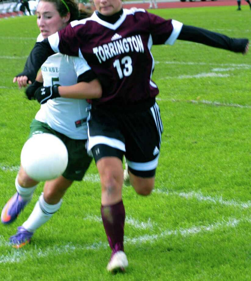 SPECTRUM/Jess Fusco of New Milford High School girls' soccer is clotheslined by an opponent during an Oct. 16, 2010 match vs. Torrington at NMHS. Photo: Norm Cummings / The News-Times