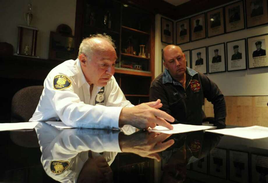 Joe Kaliko, president of the Cos Cob Fire Police Patrol, Inc., left, and Robert Grierson, deputy chief of the Volunteer Hose and Chemical Company, go over the outline of their concerns about housing the central fire station in their Cos Cob fire station, on Wednesday, Ocy. 27, 2010. Photo: Helen Neafsey / Greenwich Time