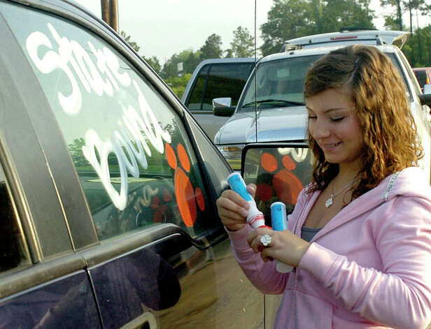 Tabitha  Wagnon puts finishing touches on a truck while waiting for the bus to arrive.  The Jasper High School baseball team left for Austin Tuesday morning on a chartered bus from their field house.  Dave Ryan/The Enterprise