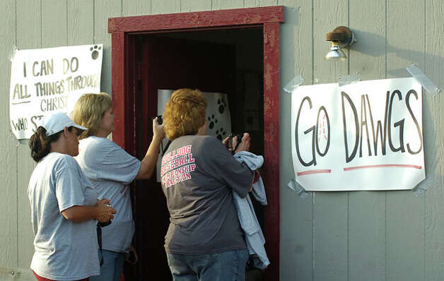 Parents, friends and fans try to take pictures through the door to the field house of the players trying to get ready to leave.  The Jasper High School baseball team left for Austin Tuesday morning to play in the state final game.  Dave Ryan/The Enterprise