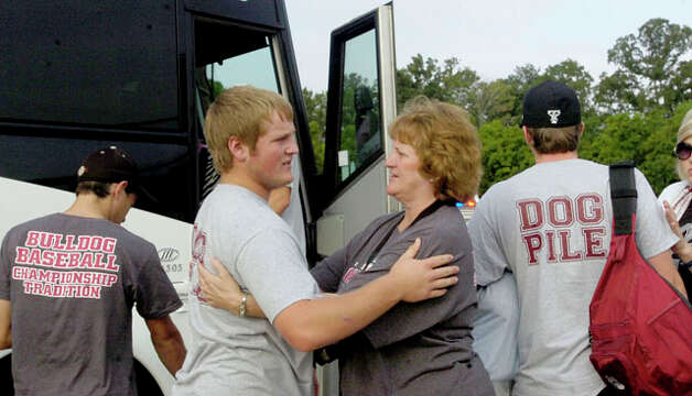 "Wynette Sowell, right, has some last words for her son, Derek ""Boomer"" Sowell, before he boarded the bus at the field house.  The Jasper High School baseball team left for Austin Tuesday morning on a chartered bus from their field house to play in the state final game.  Dave Ryan/The Enterprise"