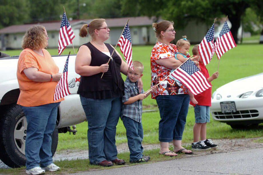 "Sour Lake residents watch as the Patriot Guard Riders lead a procession route to a memorial service honoring  Sgt. Leston ""Tony"" M. Winters, 30, of Sour Lake, Texas. Winters died July 15 in Kandahar, Afghanistan, of wounds sustained when enemy forces attacked his unit with an improvised explosive device. Processional.Tuesday, July 26, 2010. Valentino Mauricio/The Enterprise"
