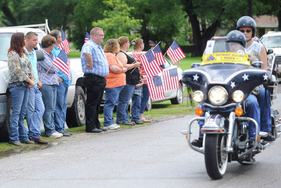 "Sour Lake residents watch as the Patriot Guard Riders lead a procession route to a memorial service honoring  Sgt. Leston ""Tony"" M. Winters, 30, of Sour Lake, Texas. Winters died July 15 in Kandahar, Afghanistan, of wounds sustained when enemy forces attacked his unit with an improvised explosive device. Tuesday, July 26, 2010. Valentino Mauricio/The Enterprise"