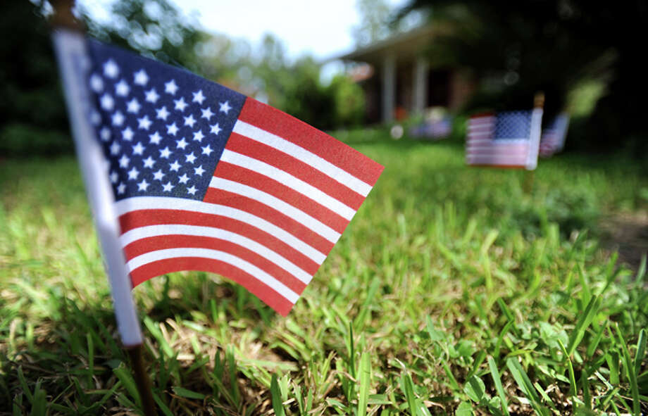 """Flags are placed in the yard of Cheryl Spivey in Sour Lake, Friday. Spivey's son, Army Sgt. Leston """"Tony"""" Micheal Winters was killed by an IED in Afghanistan Thursday.  Tammy McKinley/The Enterprise"""