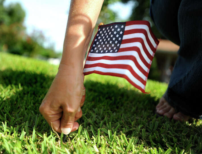 Cheryl Spivey places flags in her yard in Sour Lake, Friday. Spivey's son, Army Sgt. Leston