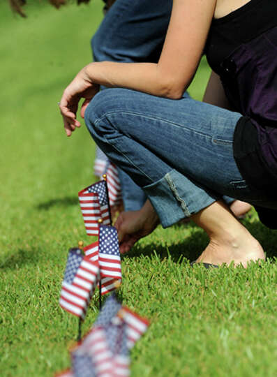 Alisha Martin places flags in her mother's yard in Sour Lake, Friday. Martin's brother, Army Sgt. Le