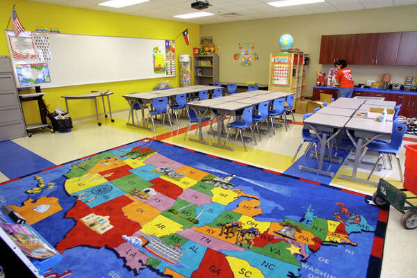 Kathleon Pinney puts things away in her new 2ed grade  room. The brand new Amelia Elementary School on Major Drive had their grand opening and dedication Friday morning.   Dave Ryan/The Enterprise
