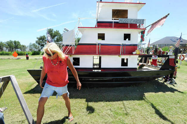 "Sabine Pass resident  Michael ""Cappy"" Deslatte walks past  a replica of  his fishig boat that he constructed with found debris from around Sabine Passs. Deslatte has compiled a heaping helping of junk he has turned into folk art. His yard, a drive- through mini theme park,  is loaded with hurricane debris that has been crafted into political statements and hilarious artwork. Saturday, July 31, 2010.  Valentino Mauricio/The Enterprise"