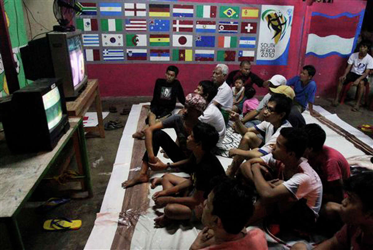 Indonesian men sit on the floor as they watch the first match of the soccer World Cup between South Africa and Mexico in Jakarta, Indonesia, on Friday. (AP Photo/Irwin Fedriansyah)