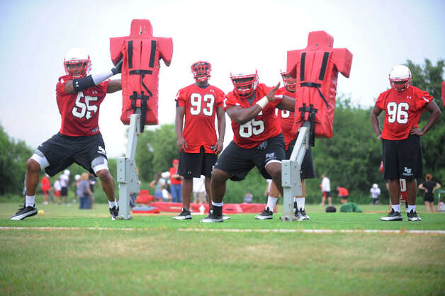 Cardinal defensive players work the blocking dummies on the first day of practice at the Coach Vernon Glass Field of Champions.  Valentino Mauricio/The Enterprise Thursday, August 5, 2010.