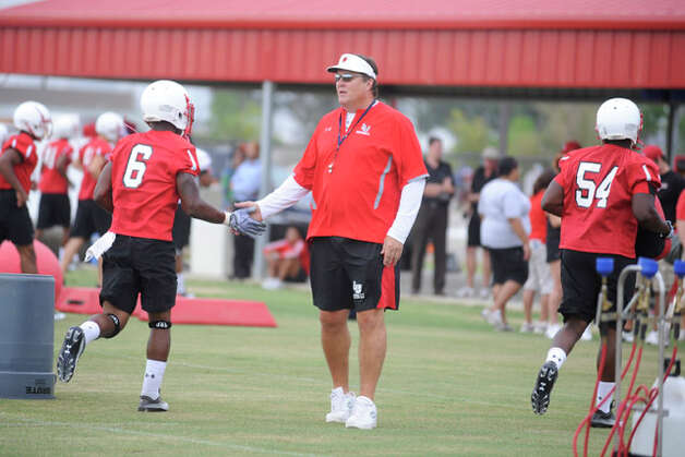 Lamar head football coach Ray Woodard, center, welcomes his players on the first day of practice at the Coach Vernon Glass Field of Champions as they prepare for their first game since the 1989 season.  Valentino Mauricio/The Enterprise Thursday, August 5, 2010.