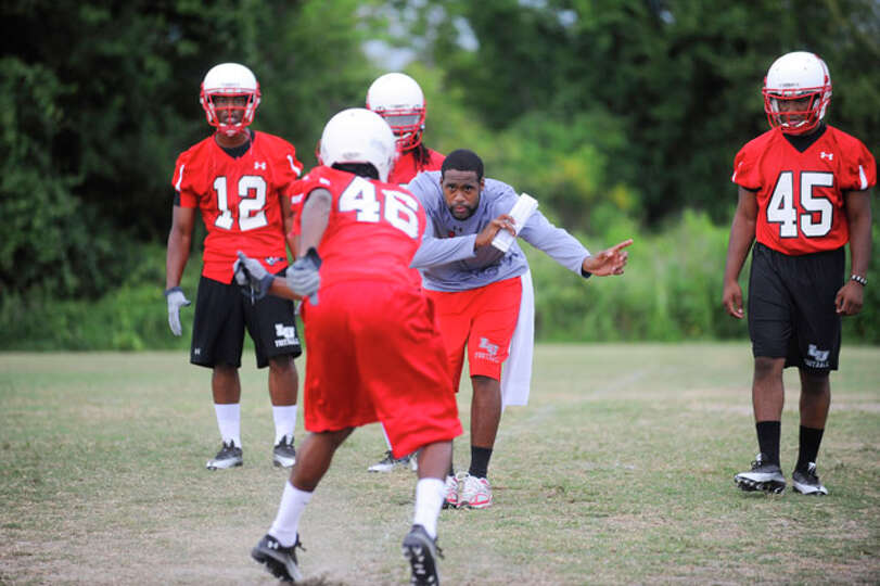 Lamar assistant coach Patrick Resby, center, works with defensive players  during Lamar University's