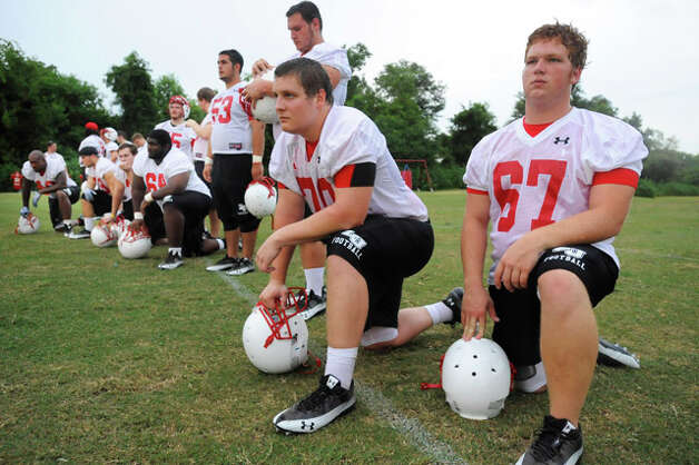 Lamar offensive linemen catch a breather in between plays during Lamar University's first football practice at the Vernon Glass Field of Champions.  Thursday, August 5, 2010. Valentino Mauricio/The Enterprise
