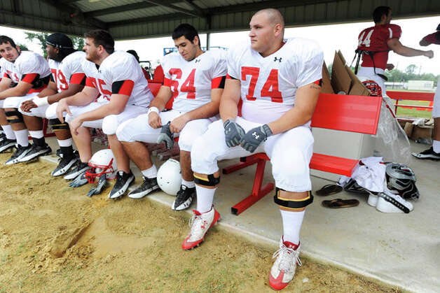 Lamar University offensive lineman Alex Goff, far right, gets ready for Wednesday's practice with Kyle Gillam, left, and offensive lineman teammates at the Vernon Glass Field of Champions.  August 11, 2010  Valentino Mauricio/The Enterprise