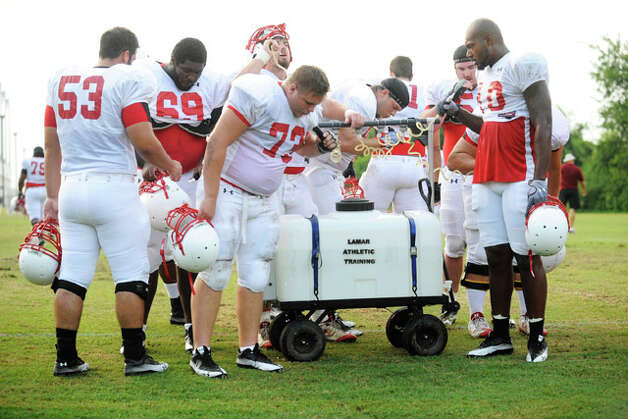 Lamar offensive linemen take a quick break to rehydrate in the high temps and humidity on Wednesday during practice at the Vernon Glass Field of Champions.  August 11, 2010  Valentino Mauricio/The Enterprise
