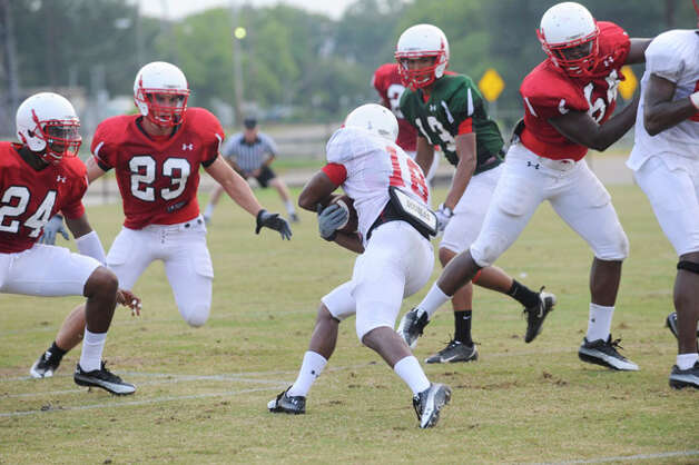 Cardinal wide receiver Donte Lopez, center,  tries to find room for yardage during practice on Wednesday at the Vernon Glass Field of Champions.  August 11, 2010  Valentino Mauricio/The Enterprise