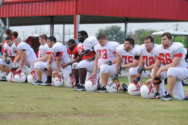 Cardinals offensive linemen watch the action  from the sidelines during practice on Wednesday at the Vernon Glass Field of Champions.  August 11, 2010  Valentino Mauricio/The Enterprise