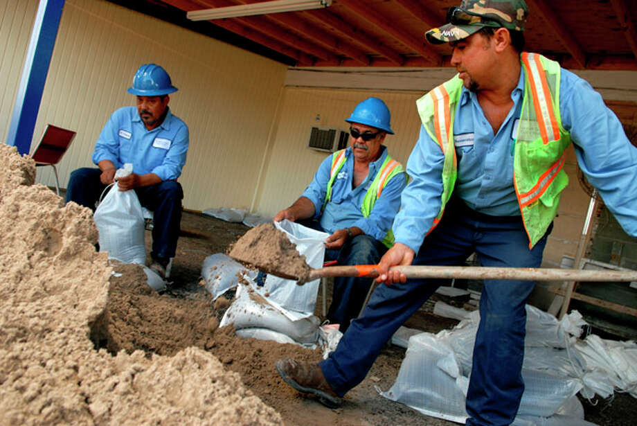 From left, Ovidio Cisneros, Felipe Mendez and Juan A Benavidez, Cameron County Works Department employees for Precinct No. 1, fill sandbags in preparation of Hurricane Alex. Beachgoers began to cancel hotel rooms for the busy July Fourth weekend Monday as officials prepared emergency shelters and sandbag distribution. / The Brownsville Herald