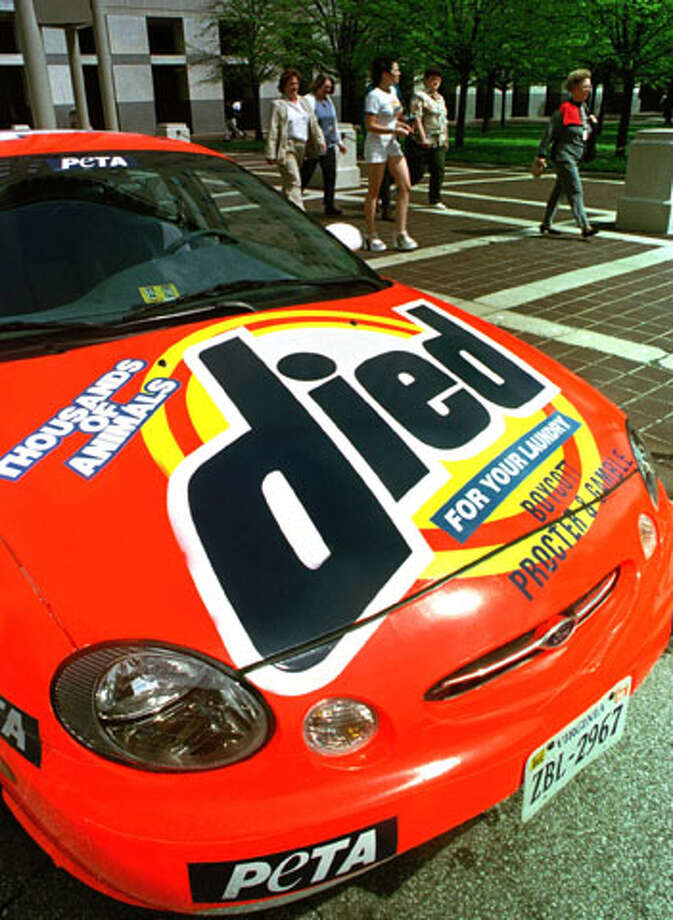 "Members of People for the Ethical Treatment of Animals hand out flyers next to their ""Died"" car they parked on the street outside Procter & Gamble's world headquarters in downtown Cincinnati on April 16, 1998. The car is a similar to the ""Tide"" race car touring the NASCAR circut. (AP Photo/Tom Uhlman)"