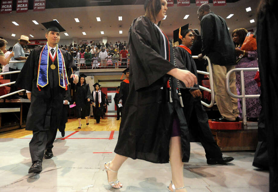 Graduates walk in the processional during graduation ceremonies in the Montagne Center at Lamar University in Beaumont, Saturday. Tammy McKinley/ The Enterprise